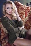 Blonde Frau der Junge recht in der warmen Strickjacke zu Hause Stockbild