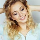 Blonde Frau der Junge recht, die auf Weiß lächelt Stockfotos