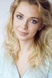 Blonde Frau der Junge recht, die auf weißem Hintergrundabschluß herauf Make-up, Lebensstilleutekonzept lächelt Stockfotografie