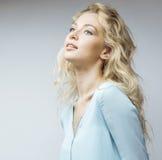 Blonde Frau der Junge recht, die auf weißem Hintergrundabschluß herauf Make-up, Lebensstilleutekonzept lächelt Stockfotos
