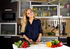 Blonde Frau der Junge recht, die Fische in der Küche kocht Stockfotos