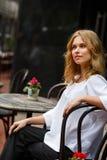 Blonde Frau der Junge recht, die im Café in der Tageszeit sitzt Stockfoto