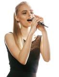 Blonde Frau der Junge recht, die im Mikrofon singt Stockbild