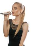 Blonde Frau der Junge recht, die im Mikrofon singt Lizenzfreie Stockfotografie