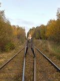 Blonde Frau der Junge recht, die nahe Eisenbahn geht Stockfotografie