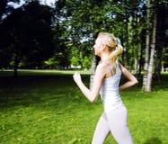 Blonde Frau der Junge recht, die Sport im Park am sonnigen Tag am Sommer, Lebensstilleutekonzept tut Stockfotos