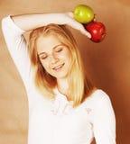 Blonde Frau der Junge recht, die zwischen dem roten und grünen lächelnden Apfel, Lebensstilleutekonzept wählt Lizenzfreie Stockfotos