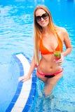 Blonde Frau der Junge recht in einem orange Bikini und Sonnenbrille genießt Stockfotografie