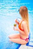 Blonde Frau der Junge recht in einem orange Bikini und Sonnenbrille genießt Lizenzfreies Stockbild