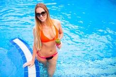 Blonde Frau der Junge recht in einem orange Bikini und Sonnenbrille genießt Lizenzfreie Stockbilder