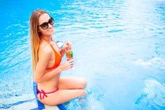 Blonde Frau der Junge recht in einem orange Bikini und Sonnenbrille genießt Stockfoto