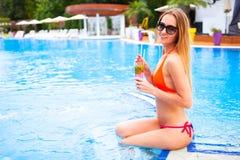 Blonde Frau der Junge recht in einem orange Bikini und Sonnenbrille genießt Lizenzfreie Stockfotos