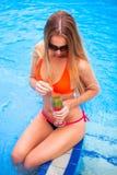 Blonde Frau der Junge recht in einem orange Bikini und Sonnenbrille genießt Lizenzfreie Stockfotografie