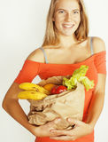 Blonde Frau der Junge recht am Einkaufen mit Lebensmittel in der Papiertüte lokalisiert auf dem Weißlächeln hell Lizenzfreie Stockfotografie