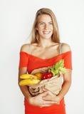 Blonde Frau der Junge recht am Einkaufen mit Lebensmittel in der Papiertüte lokalisiert auf dem Weißlächeln hell, Lebensstilleute Lizenzfreies Stockbild