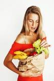 Blonde Frau der Junge recht am Einkaufen mit Lebensmittel in Papiertüteisolator Stockbild