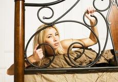 Blonde Frau der Junge recht in ihrem Schlafzimmer, das in Bett, glückliches lächelndes Lebensstilleutekonzept legt Stockbild