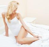 Blonde Frau der Junge recht im Bett umfasste lächelnden netten sexy Blickabschluß der weißen Blätter oben Lizenzfreie Stockfotos