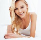 Blonde Frau der Junge recht im Bett umfasste lächelnden netten sexy Blickabschluß der weißen Blätter oben Stockfotos