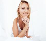 Blonde Frau der Junge recht im Bett umfasste lächelnden netten sexy Blickabschluß der weißen Blätter oben Lizenzfreies Stockbild
