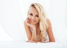 Blonde Frau der Junge recht im Bett umfasste lächelnden netten sexy Blickabschluß der weißen Blätter oben Lizenzfreie Stockbilder
