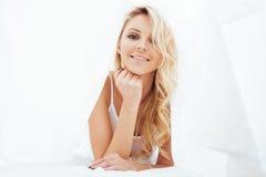 Blonde Frau der Junge recht im Bett umfasste lächelnden netten sexy Blickabschluß der weißen Blätter oben Stockfoto
