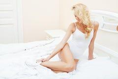 Blonde Frau der Junge recht im Bett umfasste lächelnden netten sexy Blickabschluß der weißen Blätter oben, glückliches Morgenkonz Stockbild