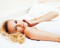 Blonde Frau der Junge recht im Bett umfasste weiße Blätter lächelndes che Lizenzfreie Stockbilder