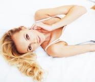 Blonde Frau der Junge recht im Bett umfasste weiße Blätter lächelndes che Stockbild