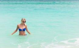 Blonde Frau der Junge recht im blauen Bikini auf weißem tropischem Strand Stockfoto