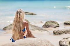 Blonde Frau der Junge recht im blauen Bikini auf weißem tropischem Strand Lizenzfreie Stockfotos