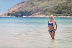 Blonde Frau der Junge recht im blauen Bikini auf weißem tropischem Strand Lizenzfreies Stockfoto