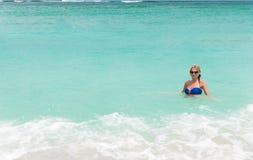 Blonde Frau der Junge recht im blauen Bikini auf weißem tropischem Strand Lizenzfreies Stockbild