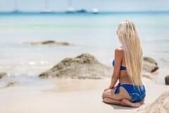 Blonde Frau der Junge recht im blauen Bikini auf weißem tropischem Strand Lizenzfreie Stockfotografie