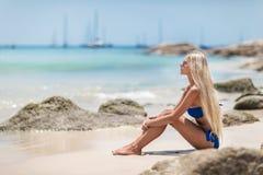 Blonde Frau der Junge recht im blauen Bikini auf weißem tropischem Strand Stockbilder