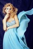 Blonde Frau der Junge recht im blauen Luxuskleid Stockfotografie