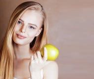 Blonde Frau der Junge recht mit dem glücklichen netten Lächeln des grünen Apfels Stockfotos