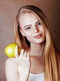 Blonde Frau der Junge recht mit dem glücklichen netten Lächeln des grünen Apfels Stockbild