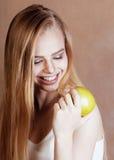 Blonde Frau der Junge recht mit dem glücklichen netten Lächeln des grünen Apfels Lizenzfreie Stockfotografie