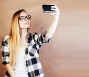 Blonde Frau der Junge recht mit dem Smartphone, der das Lächeln, machend aufwirft Stockfotos