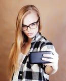 Blonde Frau der Junge recht mit dem Smartphone, der das Lächeln, machend aufwirft Stockbilder