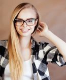 Blonde Frau der Junge recht mit dem Smartphone, der das Lächeln, machend aufwirft Lizenzfreie Stockbilder