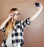 Blonde Frau der Junge recht mit dem Smartphone, der das Lächeln, machend aufwirft Lizenzfreies Stockbild