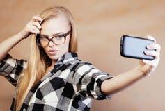 Blonde Frau der Junge recht mit dem Smartphone, der das Lächeln, selfie machend, modernes Leutekonzept des Lebensstils aufwirft Lizenzfreies Stockfoto