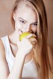 Blonde Frau der Junge recht mit glücklichem nettem lächelndem Abschluss des grünen Apfels oben auf warmem braunem Hintergrund, Le Stockbild