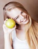 Blonde Frau der Junge recht mit glücklichem nettem lächelndem Abschluss des grünen Apfels oben auf warmem braunem Hintergrund, Le Stockfotografie