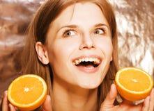 Blonde Frau der Junge recht mit halben Orangen schließen oben auf dem weißen hellen Jugendlächeln Stockfotos