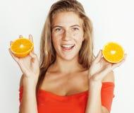 Blonde Frau der Junge recht mit halben Orangen schließen oben lokalisiert auf dem weißen hellen Jugendlächeln Lizenzfreies Stockbild