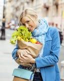 Blonde Frau der Junge recht mit Lebensmittel beim Taschengehen Stockbilder