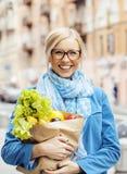 Blonde Frau der Junge recht mit Lebensmittel beim Taschengehen Lizenzfreie Stockfotografie